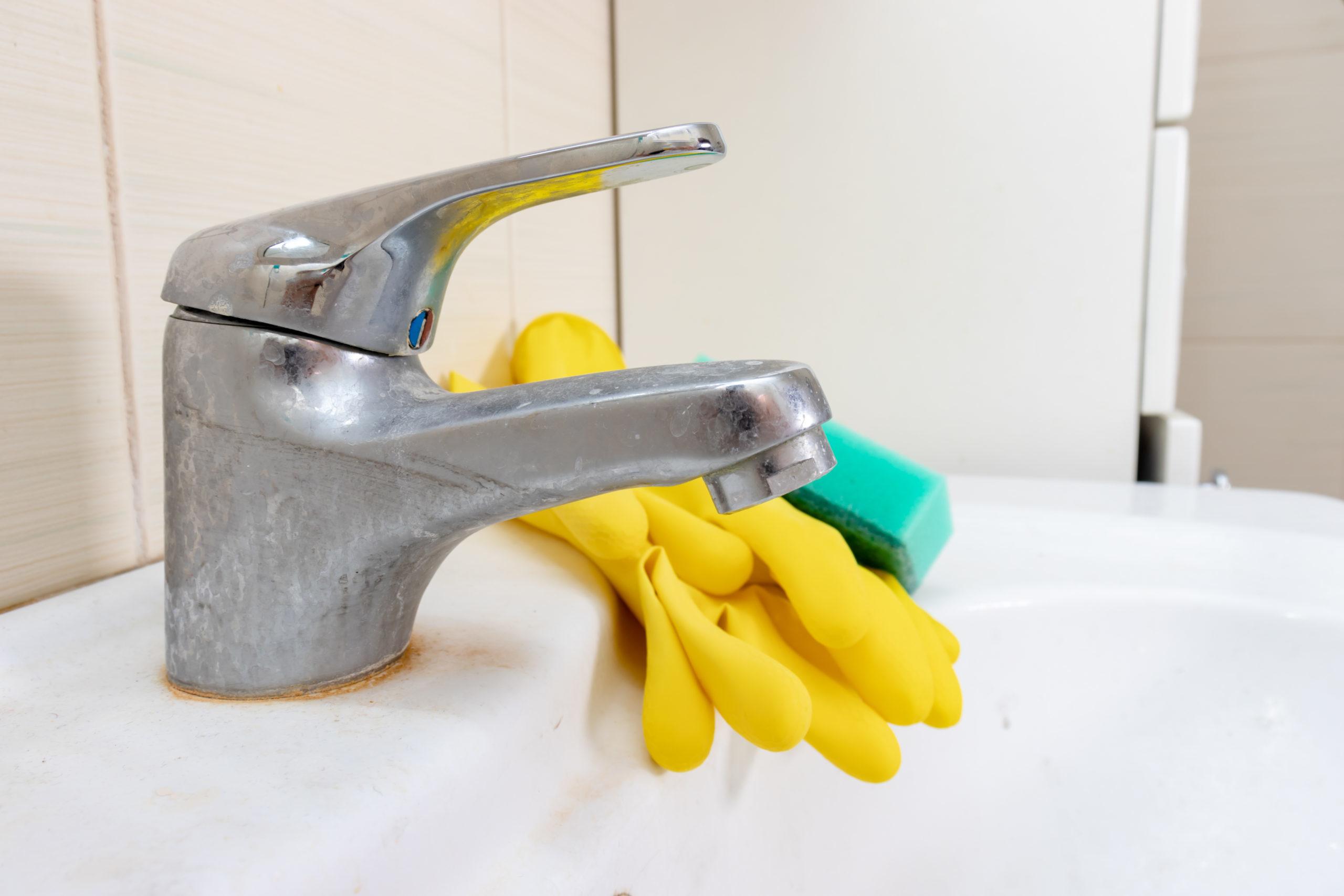 Foto eines schmutzigen Bad-Waschbeckens mit Kalkablagerungen, worauf gelbe Gummihandschuhe und ein grüner Schwamm liegen.